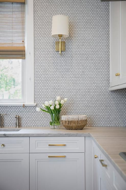 a chic neutral kitchen with a grey stone countertop and white penny tiles all over plus gold fixtures for more glam