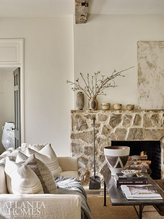 a chic neutral living room with a rough stone fireplace and neutral furniture, blooming branches that brings warmth here
