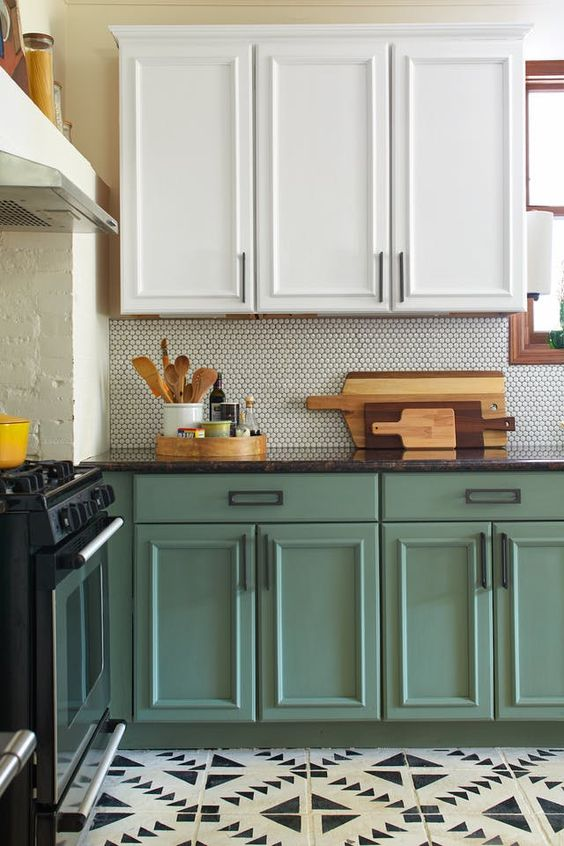 a chic two tone kitchen in green and white, with a grey penny tile backsplash and a black stone countertop