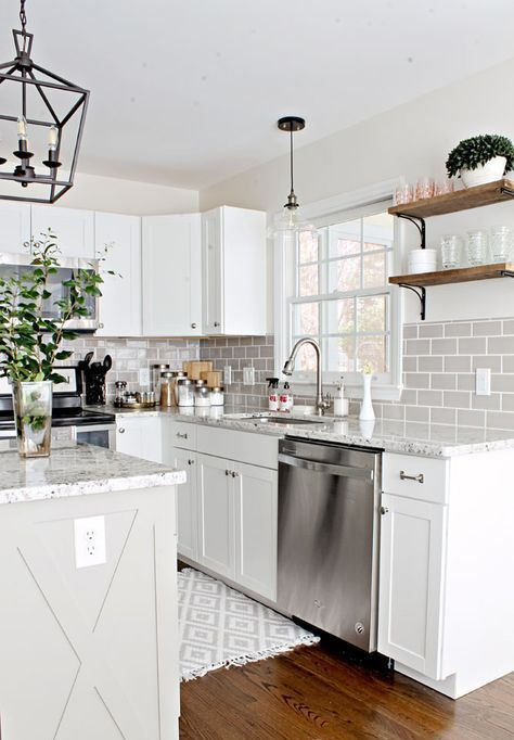 a chic white farmhouse kitchen with terrazzo countertops and a grey subway tile backsplash is very elegant