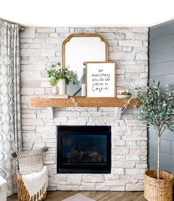 a chic whitewashed stone fireplace with a wooden mantel, askets and greenery in vases plus artworks on the mantel