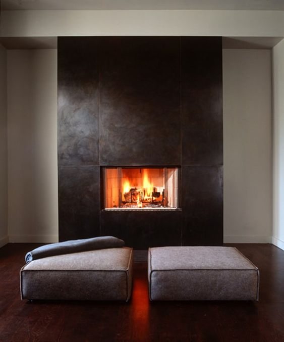 a clean and modern fireplace with sleek metal sheets that surround it and a couple of minimal cushions is a stylish idea