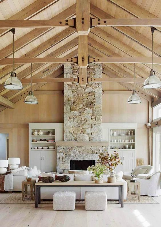 a coastal barn living room with a stone fireplace, neutral furniture and pendant lamps plus potted plants