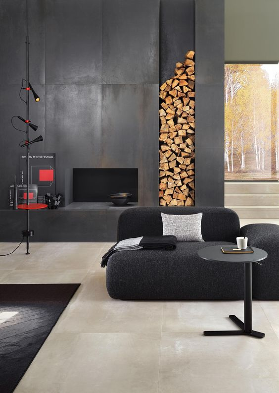 a contemporary monochromatic interior finished with a faux fireplace clad with metal sheets and with a firewood storage niche