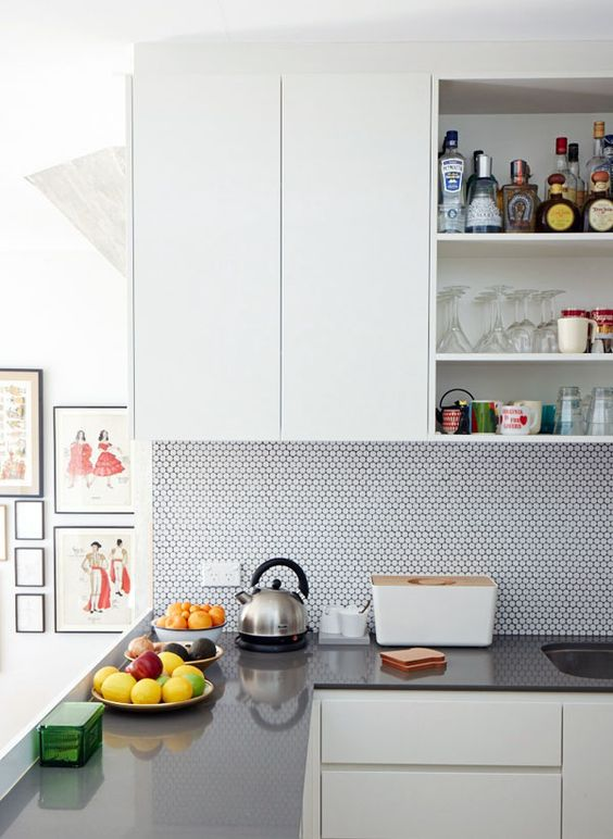 a contemporary neutral kitchen with grey stone countertops and a white penny tile backsplash is cool and airy