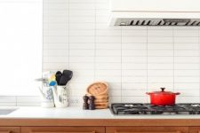 a contemporary wooden kitchen with a white hood, white countertops and a white stacked tile backsplash