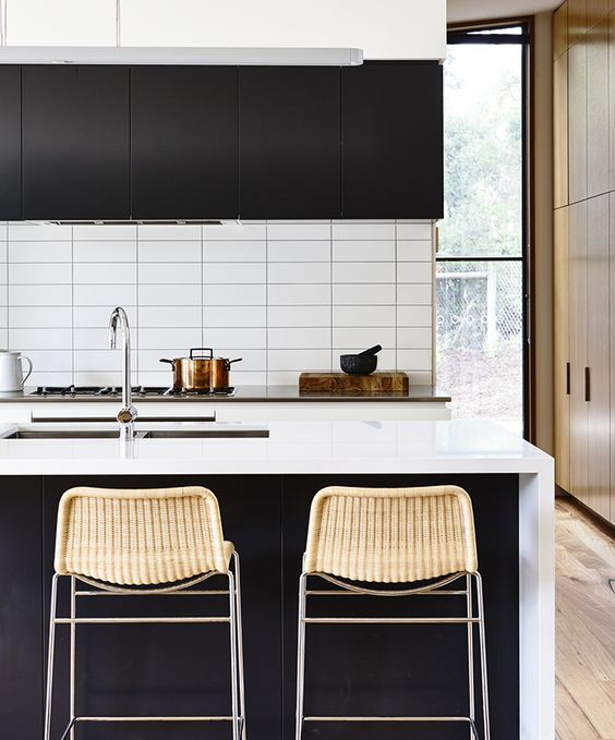 a contrasting contemporary kitchen with black cabinets, white stone countertops and a white stacked tile backsplash
