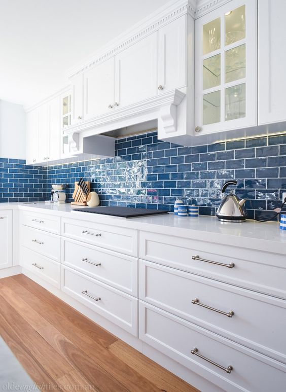 a cozy coastal kitchen in white, with bold blue subway tiles that add color and hint on the location