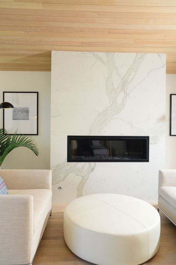 a cozy minimalist space with a white marble fireplace, neutral furniture and a wooden ceiling is very chic