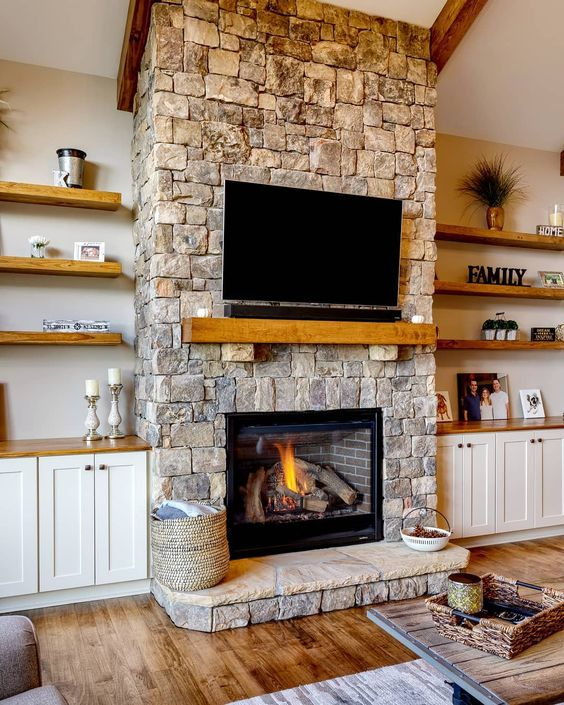 a cozy neutral living room spruced up with a stone fireplace, a wooden mantel and a TV over the fireplace