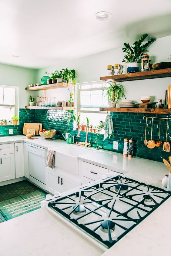 a cozy white kitchen with emerald subway tiles and wooden shelves is very bright and very stylish
