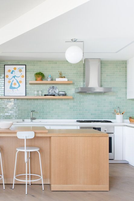 a cute white kitchen with aqua subway tiles, a wooden kitchen island and shelves and white furniture is very cool