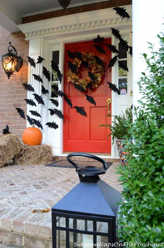 a farmhouse Halloween porch with hay, a pumpkin, a leaf wreath and lots of bats is very bold and cool