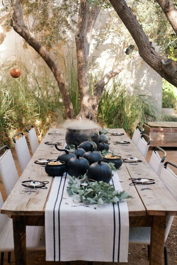 a farmhouse Halloween tablescape with black pumpkins, greenery and a cauldron as a centerpiece
