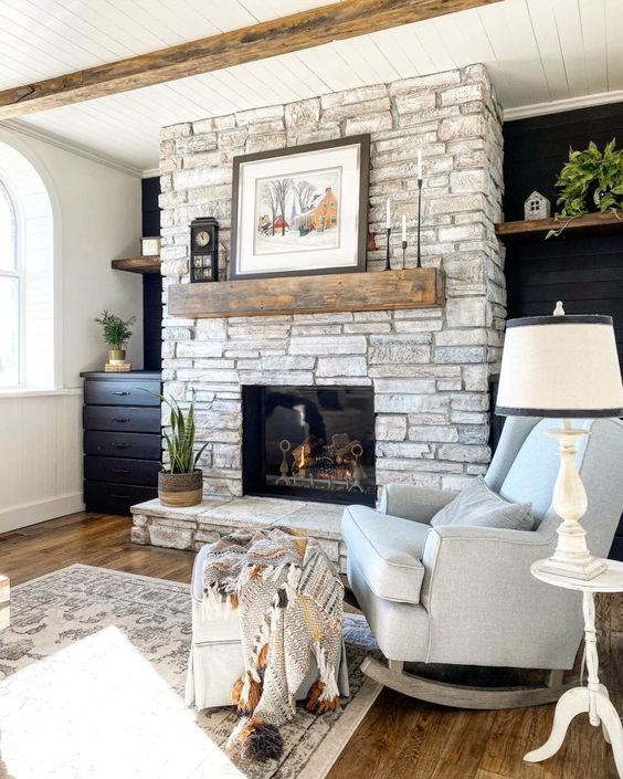 a farmhouse living room with a whitewashed stone fireplace and neutral and elegant furniture