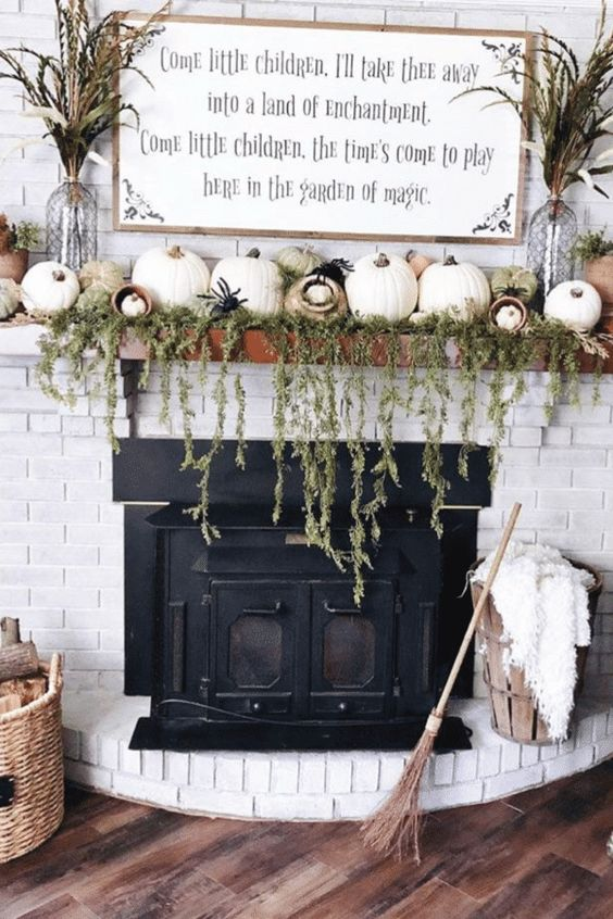 a farmhouse mantel with cascading greenery, lots of pumpkins, spiders, dried grasses and a broom