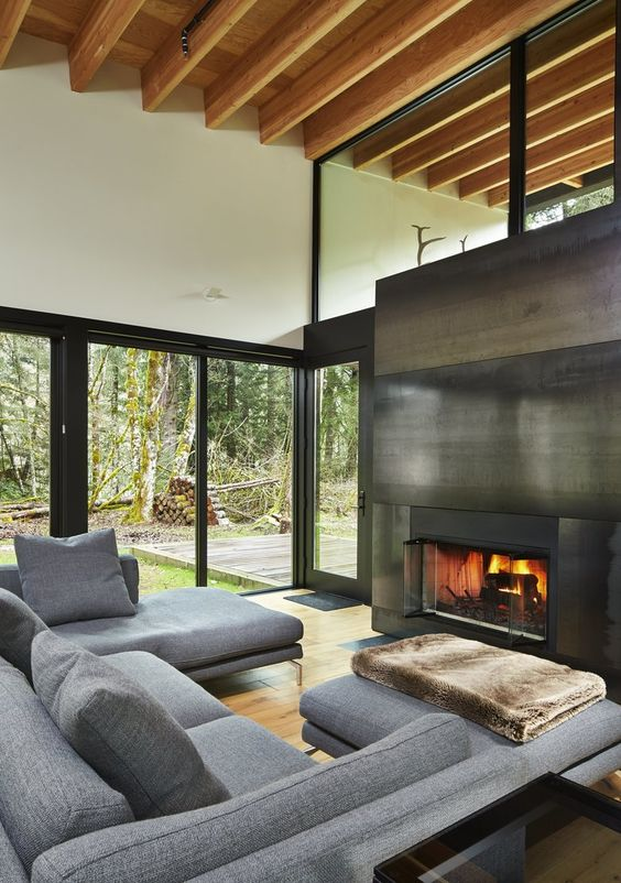 a fireplace clad with blackened steel separates the living room from the covered patio and brings coziness to the space