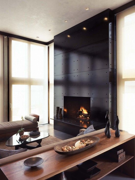 a gorgeous black steel clad fireplace with accenting screws is a beautiful statement decor feature