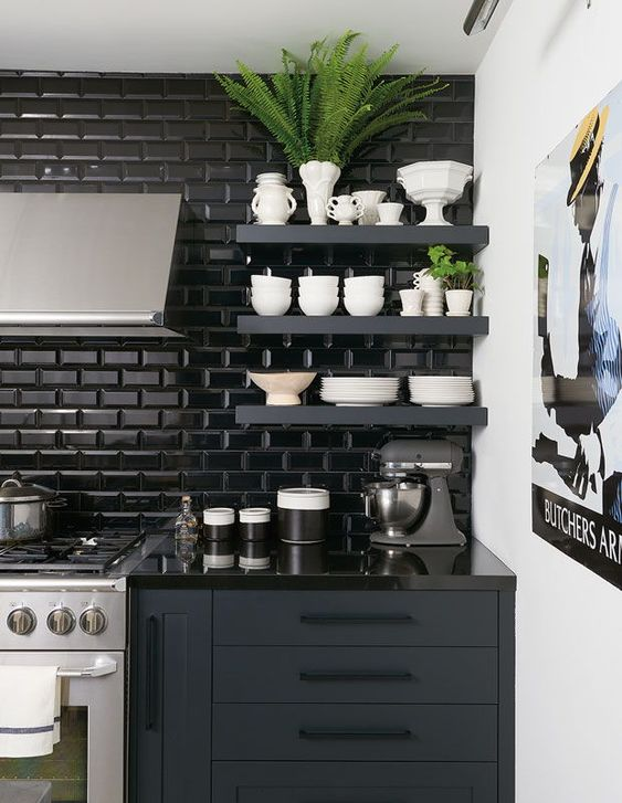 a graphite grey kitchen with black glossy subway tiles and glossy black countertops is classy and dramatic