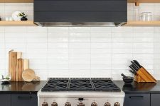 a graphite grey kitchen with wooden shelves and a white stacked tile backsplash is very chic and bold