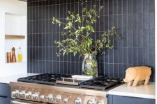 a grey kitchen with wooden beams, a black matte stacked tile backsplash and a metal cooker and hood