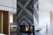 a grey marble slab fireplace separates the sleeping and bathing zone and makes them cozy and warm