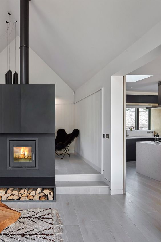 a hearth clad with dark metal makes a bold statement in this open layout and it's visible from all sides