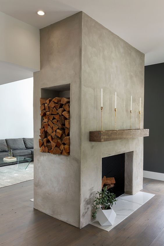 a large concrete fireplace with marble tiles, a rough wood slab, a niche for storing firewood and a potted plant