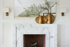 a large non-working fireplace clad with white marble and a mantel, with brass vases with green branches