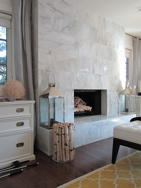 a large non-working fireplace clad with white marble tiles all over, with candle lanterns and firewood in a vase