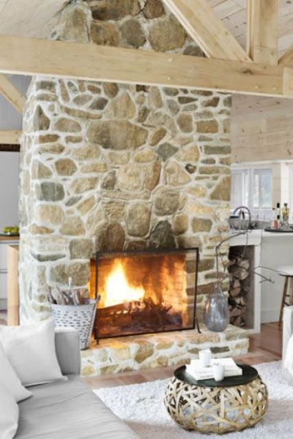 a large stone fireplace separates the kitchen and the living room and makes both of them cozier and warmer