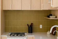 a light colored plywood kitchen with a mustard stacked tile backsplash and white fixtures for a fresh touch
