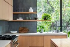 a light-colored sleek wooden kitchen with white countertops and grey stacked tiles covering walls