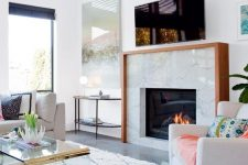 a light-filled and welcoming living room with a marble clad built-in fireplace with a wooden mantel