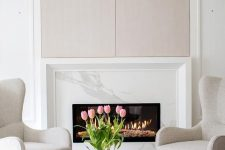 a light-filled neutral and pastel living room with a marble clad fireplace and a cool sitting zone by its side