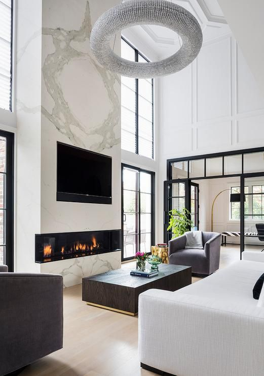 a luxurious living room with a large marble slab with a built in fireplace and a TV is the centerpiece of the room