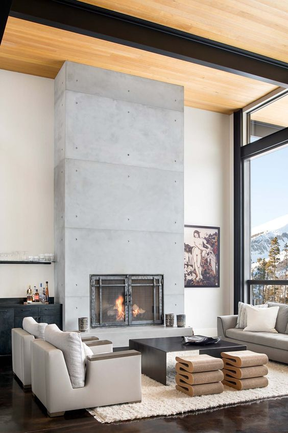 a luxurious living room with neutral furniture, catchy stools and a black table, a concrete fireplace with metal doors