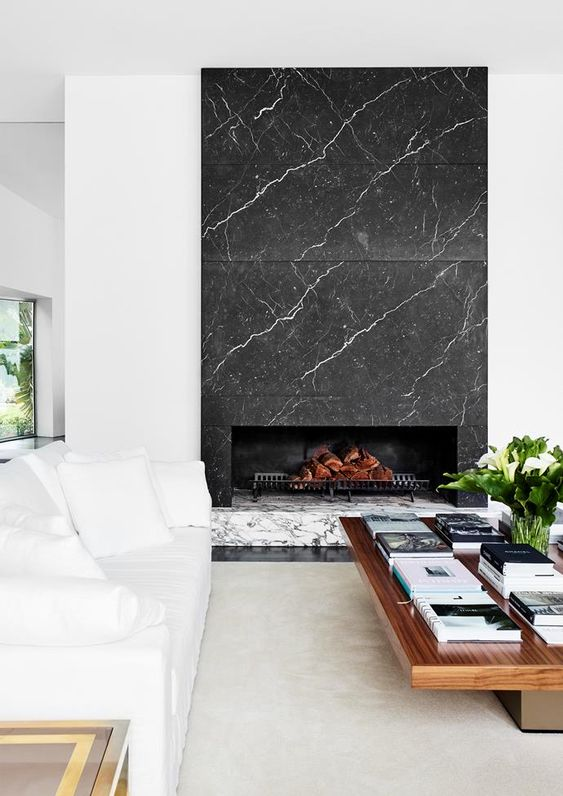 a luxurious living room with white and wooden furniture and a grey and white marble fireplace is a stylish and cool space
