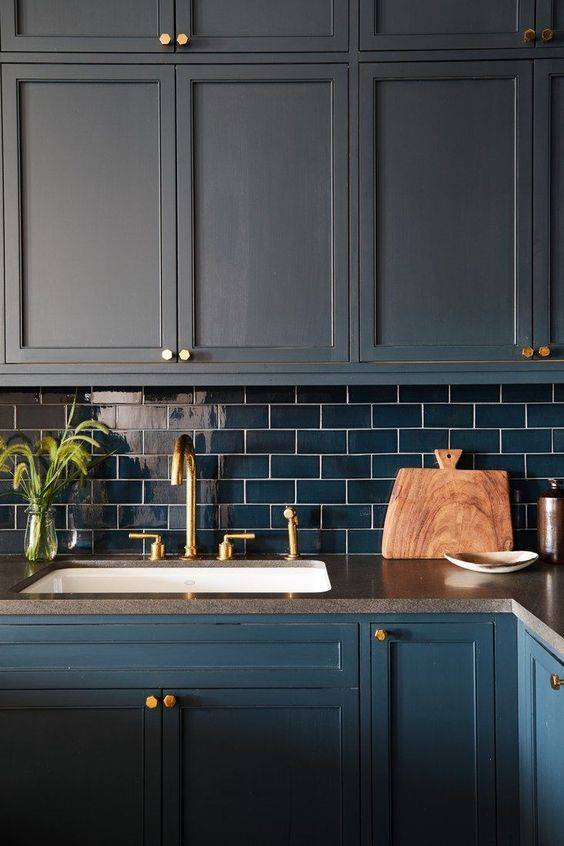 a matte navy kitchen with navy subway tiles and gold touches for a bold and dramatic kitchen in dark shades