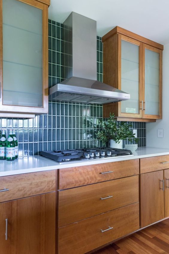 a mid-century modern wooden kitchen with a glossy blue stacked tile backsplash and frosted glass cabinets
