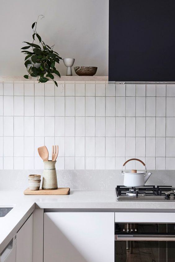 a minimalist grey kitchen with a navy hood, wooden shelves and a white stacked tile backsplash