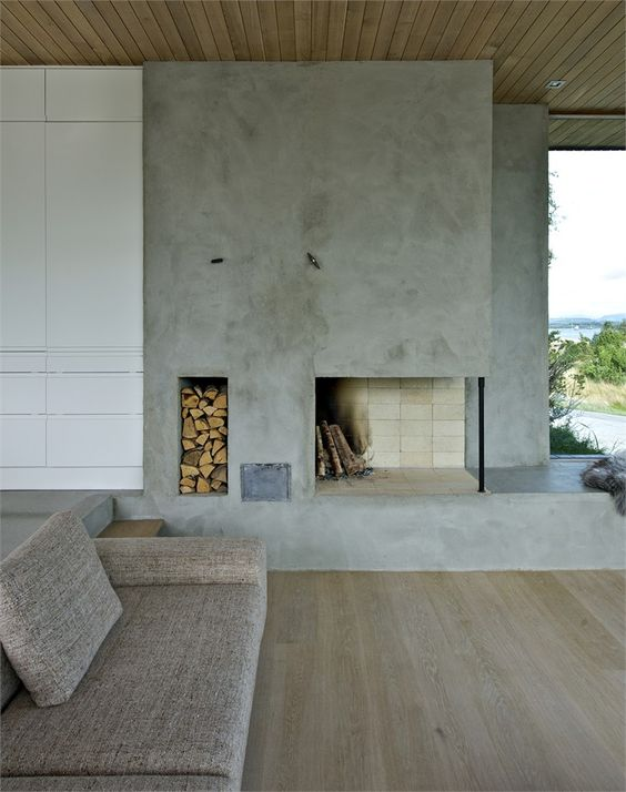 a minimalist living room with a concrete fireplace, a niche for firewood storage and simple furniture