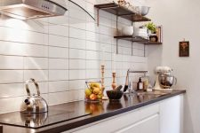 a minimalist white kitchen with a white stacked tile wall, black countertops and shelves is very chic