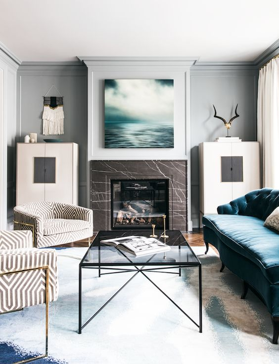 a modern chic living room with a fireplace clad with brown marble, with a glass table and a blue sofa is dreamy