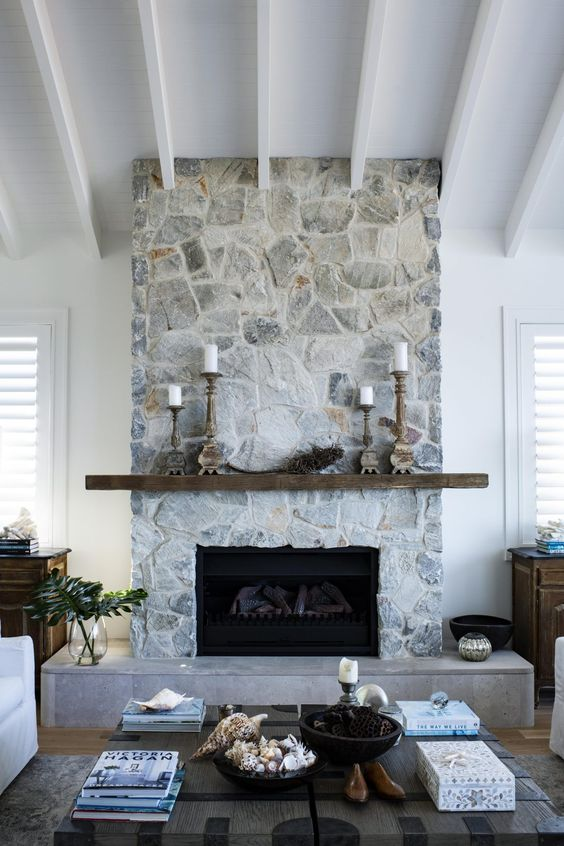 a modern coastal living room warmed up with a whitewashed stone fireplace, a rough wooden mantel and wooden candle holders