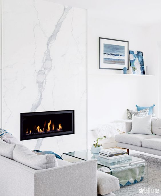 a modern coastal living room with a white marble fireplace, neutral furniture and blue accents for a beachy feel