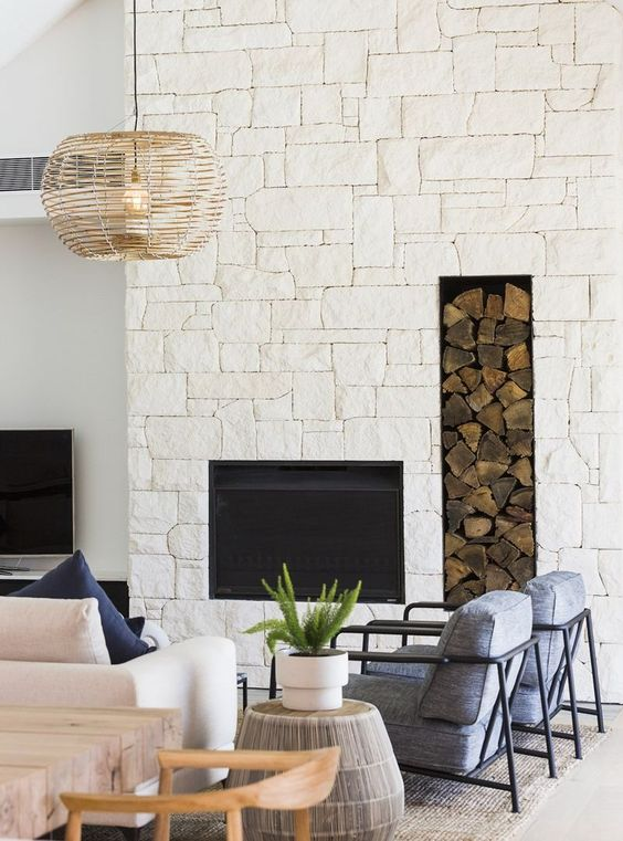 a modern coastal living room with an oversized white stone fireplace, a niche for firewood for a more welcoming feel