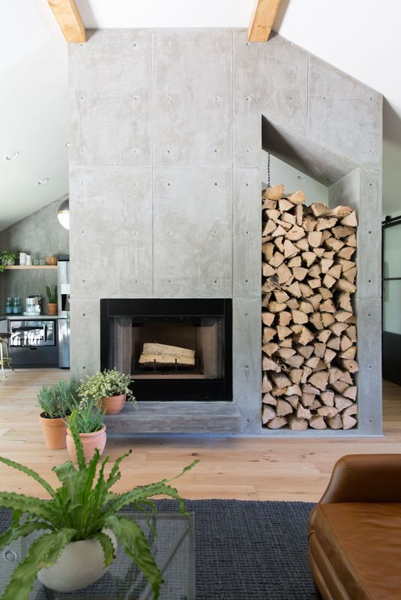 a modern concrete fireplace with an oversized nich for storing firewood is a cool statement for any space