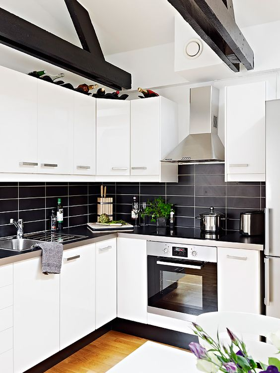 a modern contrasting kitchen with white cabinets, a black stacked tile backsplash and metal countertops is extra bold