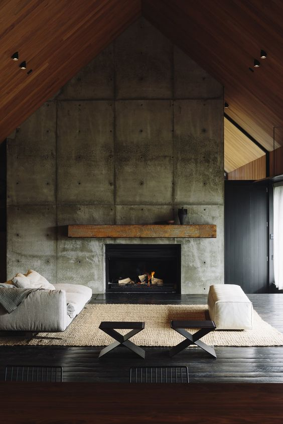 a modern industrial living room with an oversized concrete fireplace and a rough wooden mantel plus comfy furniture